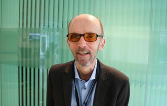 Glad mann med oransje filterbriller, lysegrønn og lett gjennomsiktig bakgrunn.