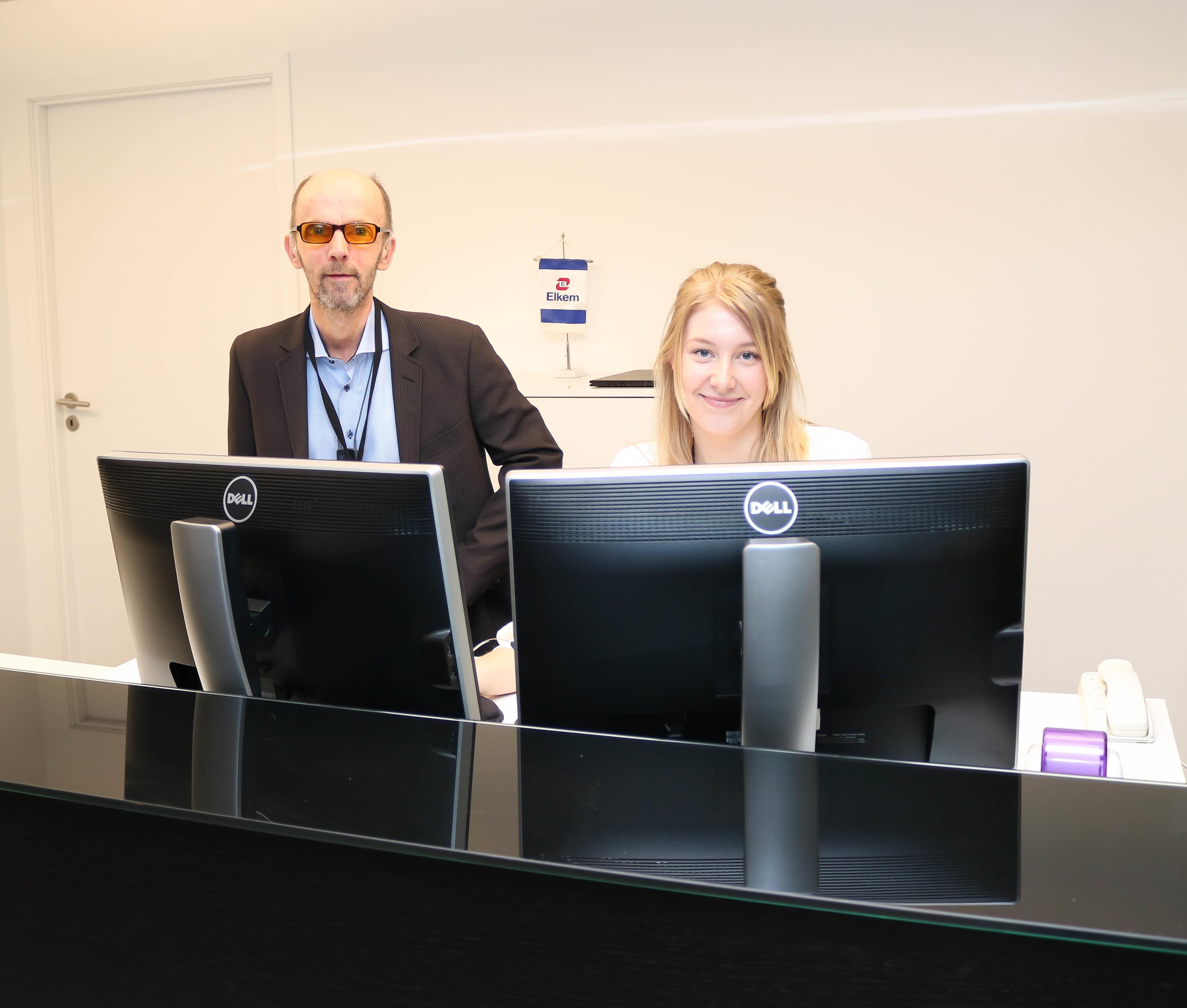 Mann med oransje filterbriller og lyshåret kvinne bak to store dataskjermer.