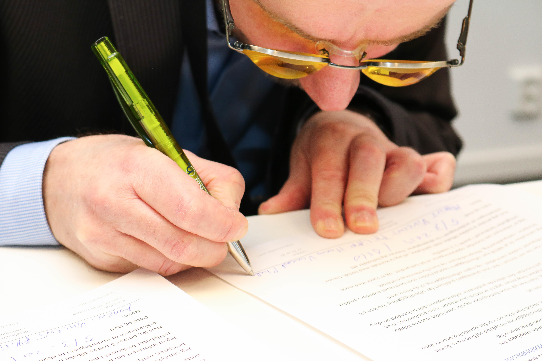 Nærbilde av mann med oransje filterbriller som skriver på et ark med en grønn penn.