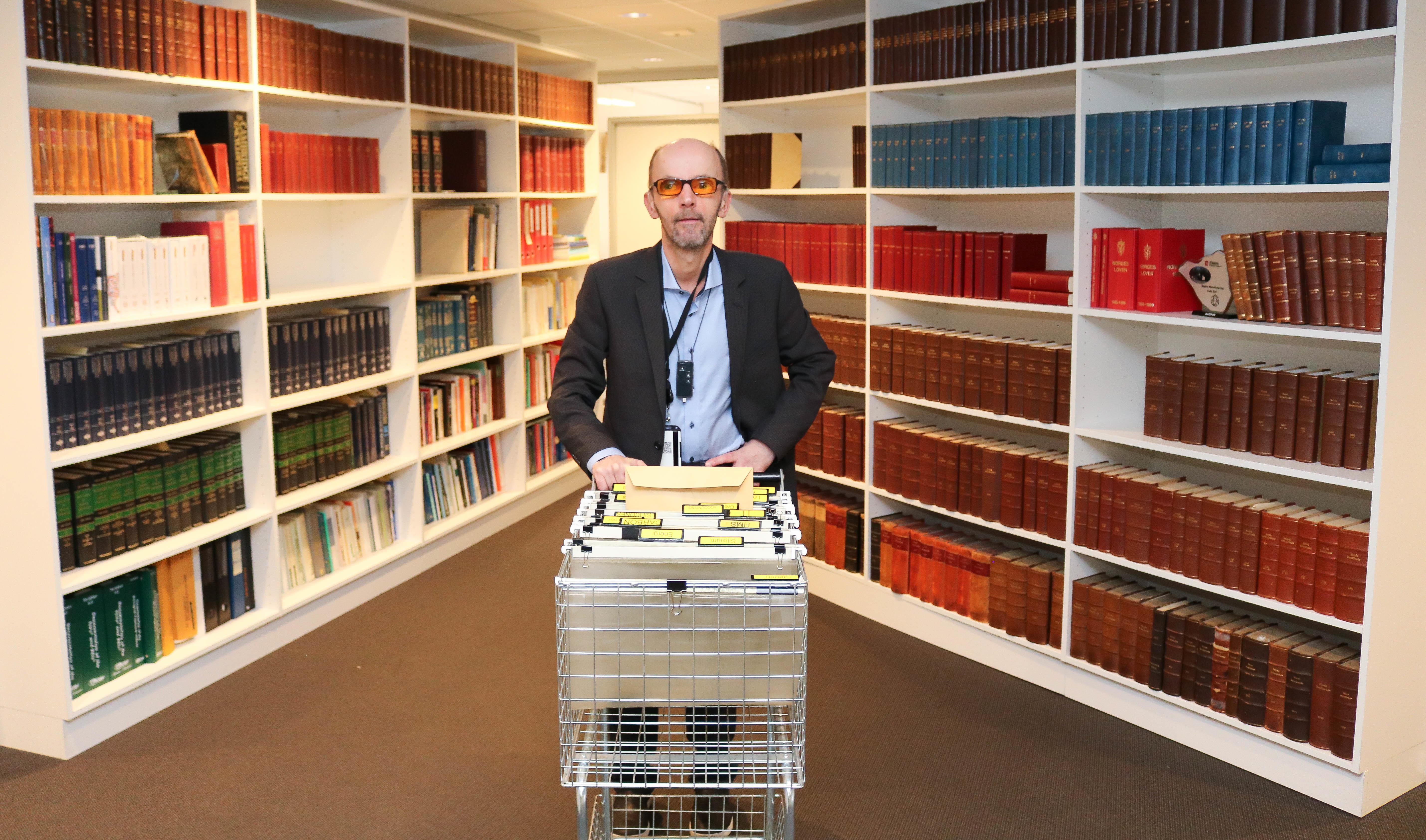 Midt i et bibliotek. Mann med filterbriller står med en postvogn mellom to skråstilte bokhyller.