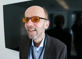 Mann med oransje filterbriller smiler stort i forgrunnen av en svart tv-skjerm.