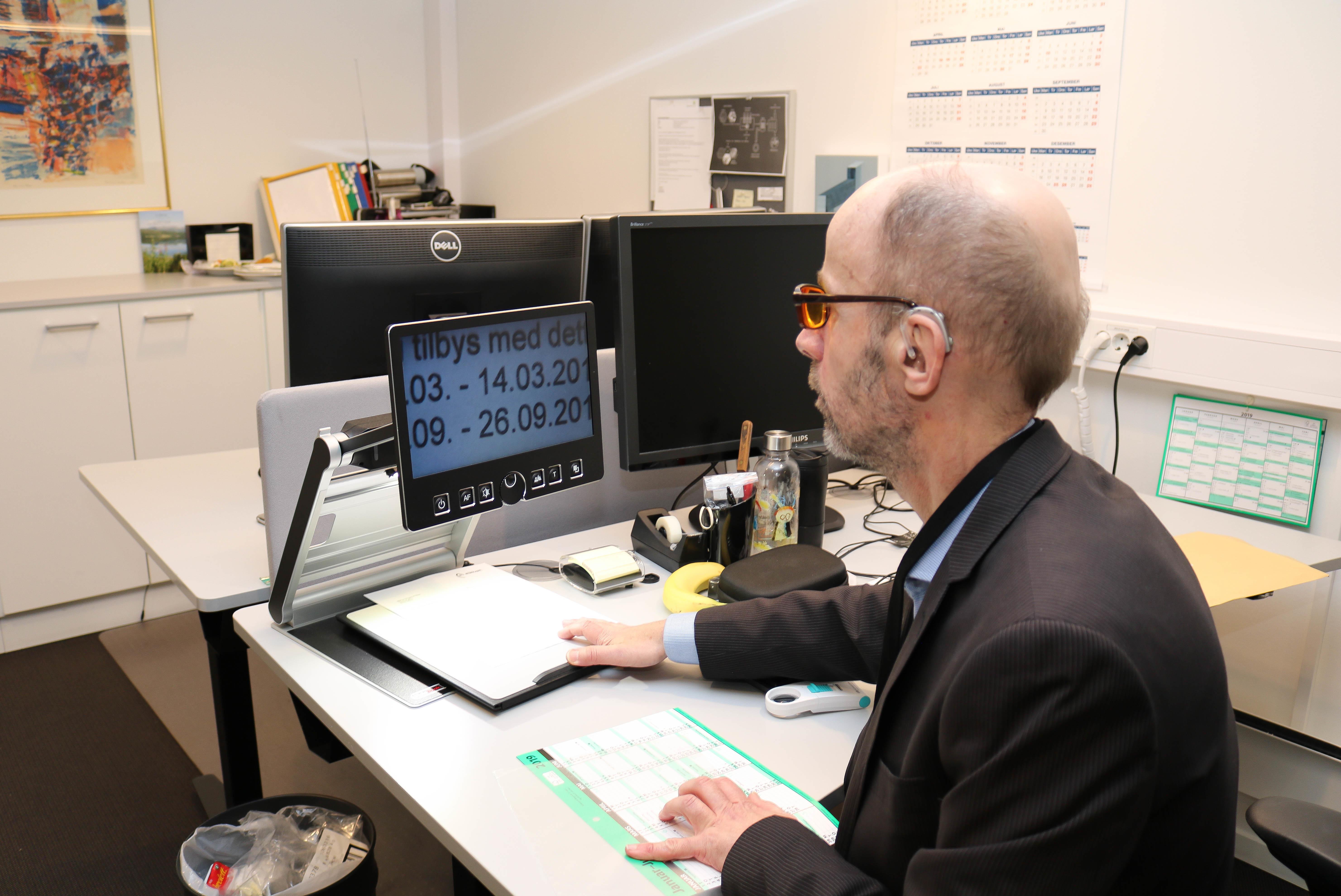 Bruk av forstørrelsesprogram og tilpasset skjerm for lesing av tekster. Bruker er mann med oransje filterbriller.