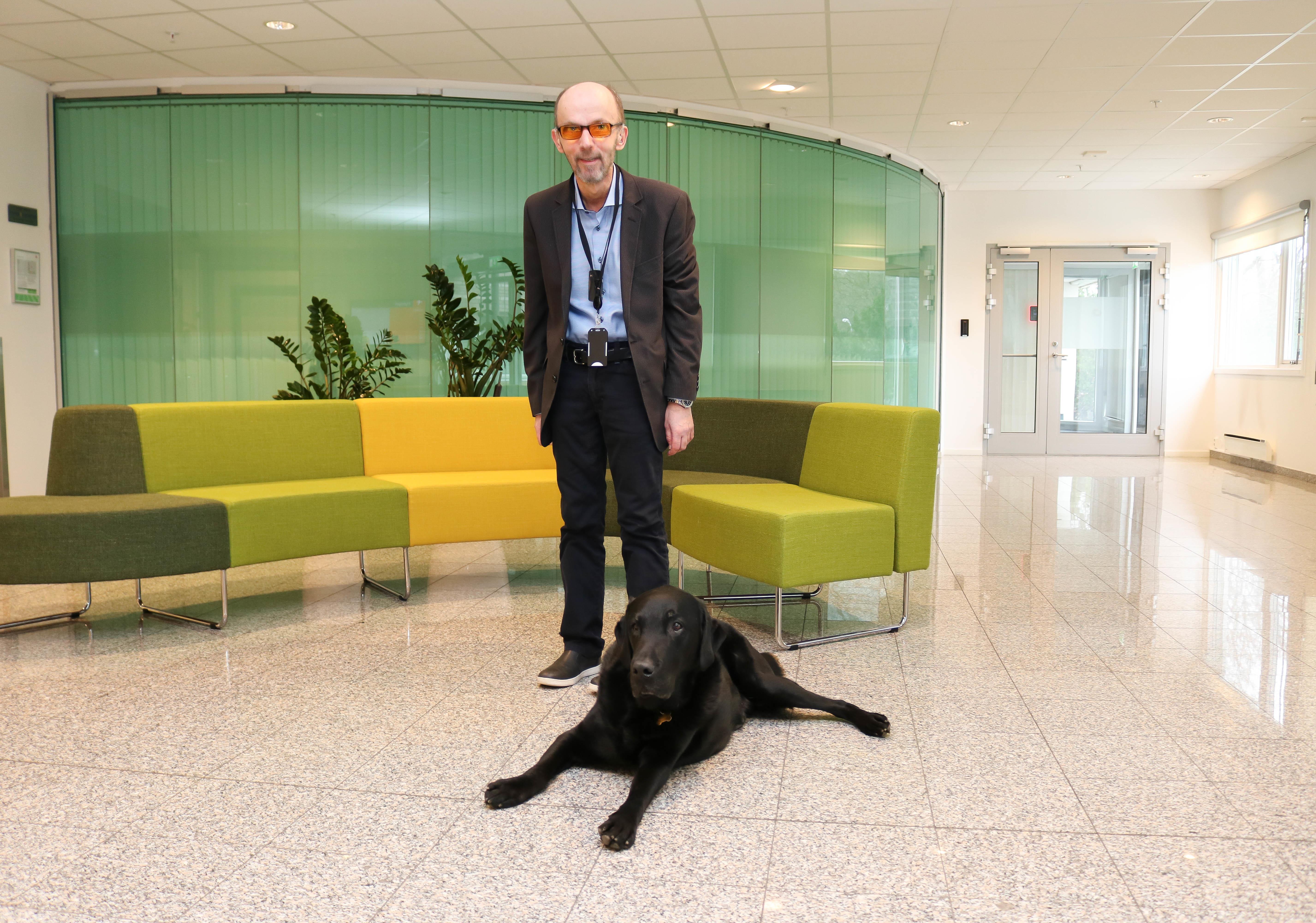 Mann med oransje filterbriller og liggende svart hund i åpent resepsjonslokale.