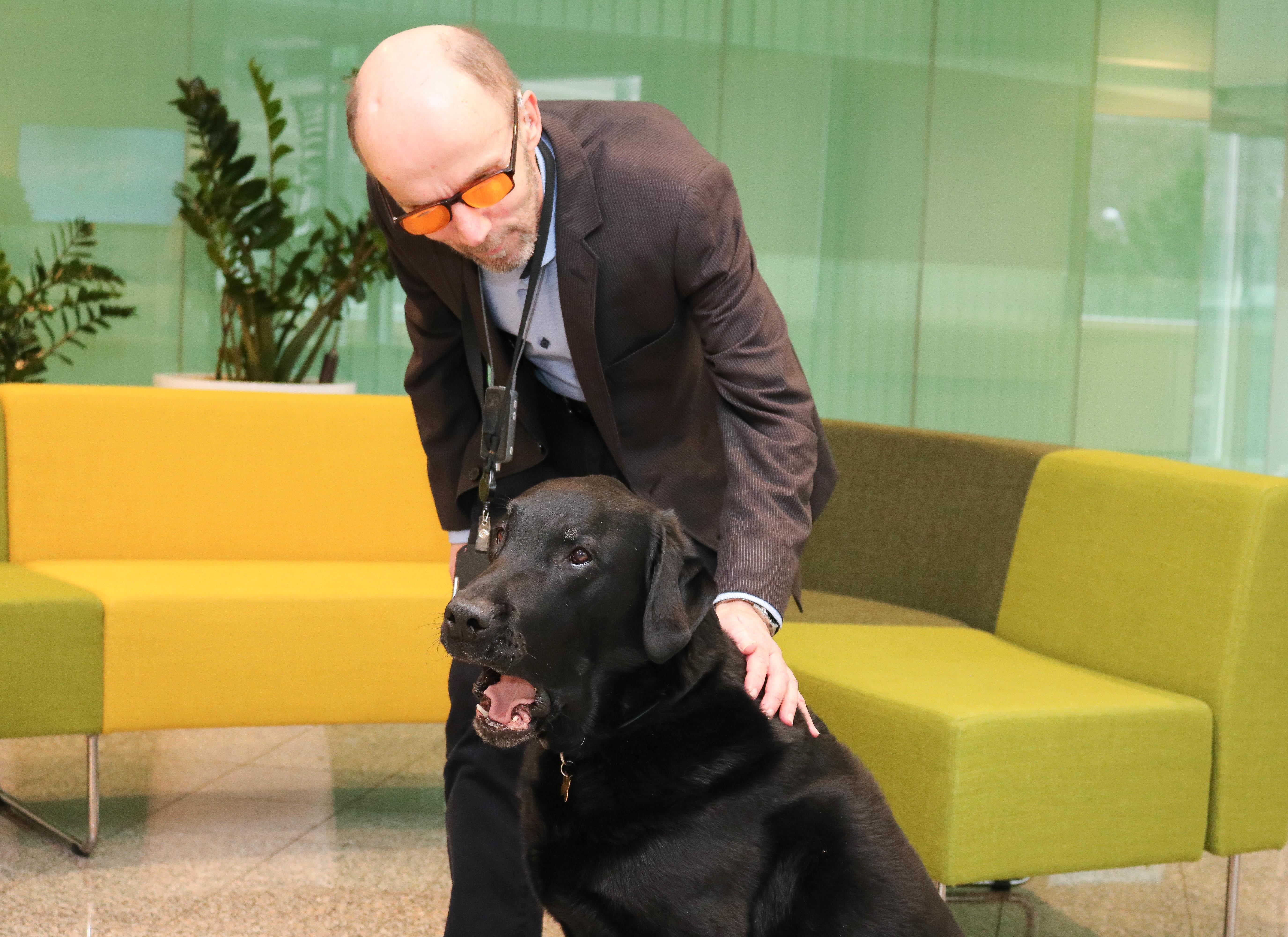 Mann med oransje filterbriller klapper varsomt svart labrador i åpent resepsjonslokale.