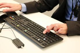 Døvblind mann skriver på tilpasset datatastatur. En lyd- og taleforsterker ligger i forkant av tastaturet.