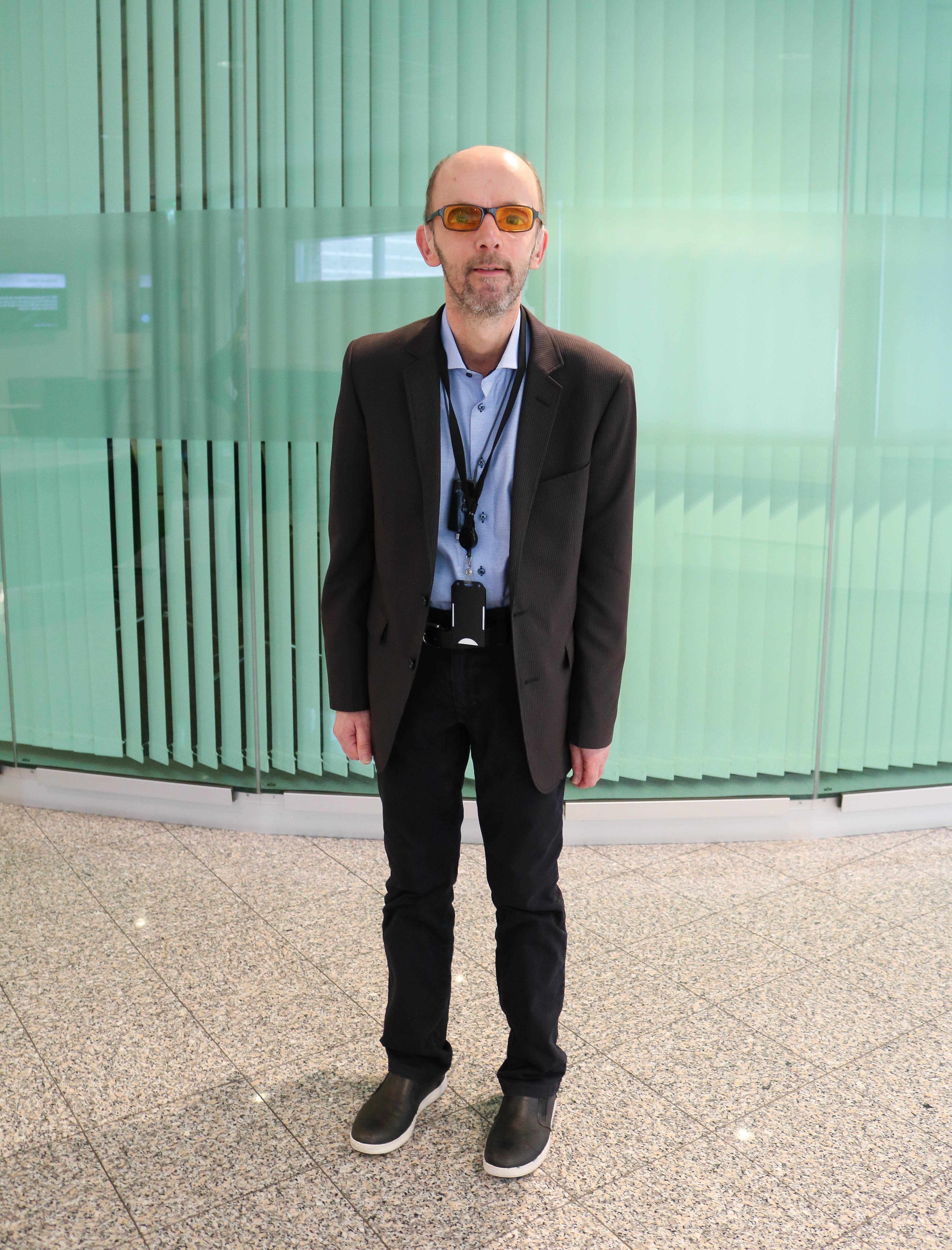 Portrettbilde av døvblind mann med oransje filterbriller. Han står foran en grønn, lett gjennomsiktig vegg.
