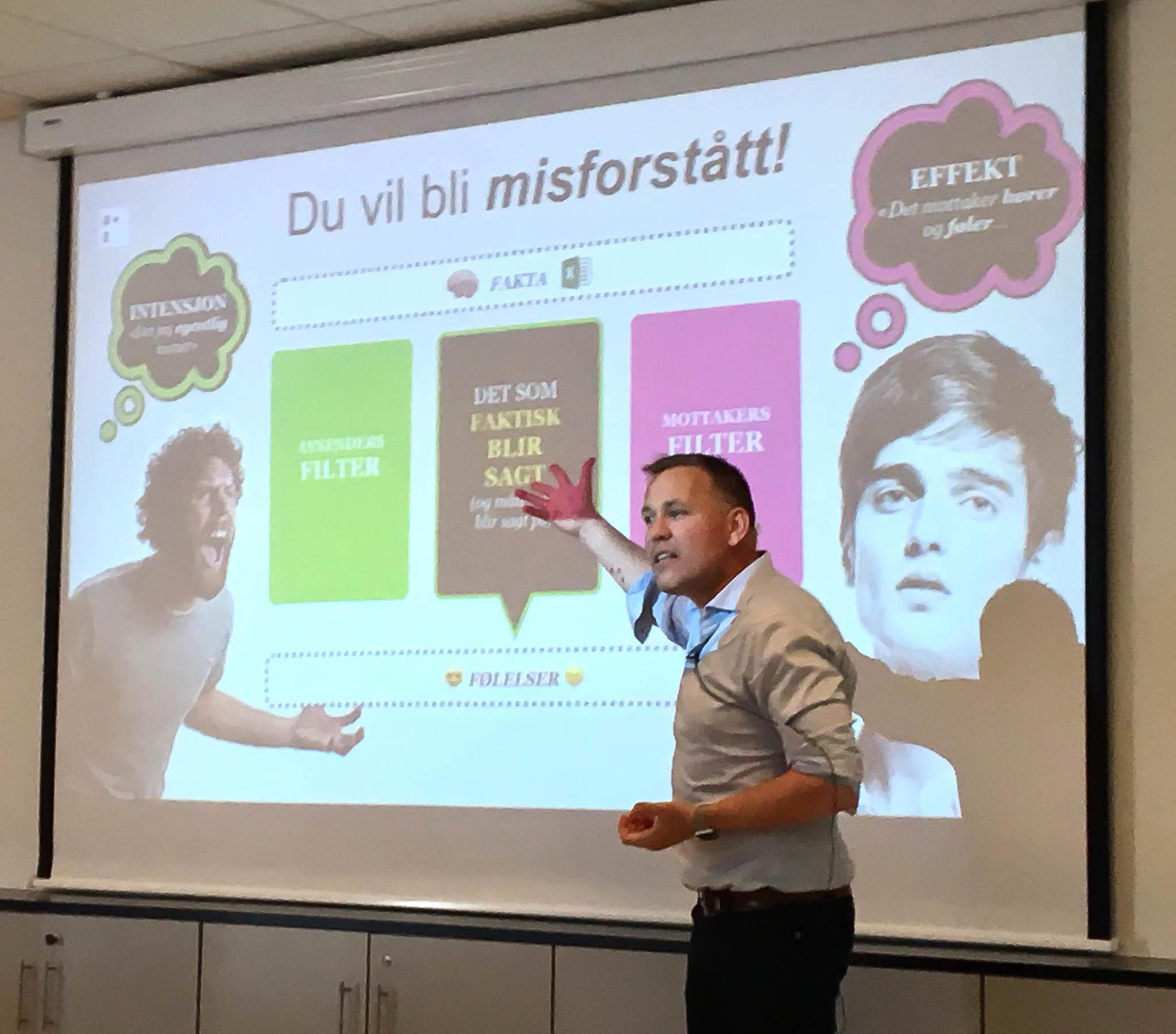 Mann foreleser foran en stor skjerm med overskriften