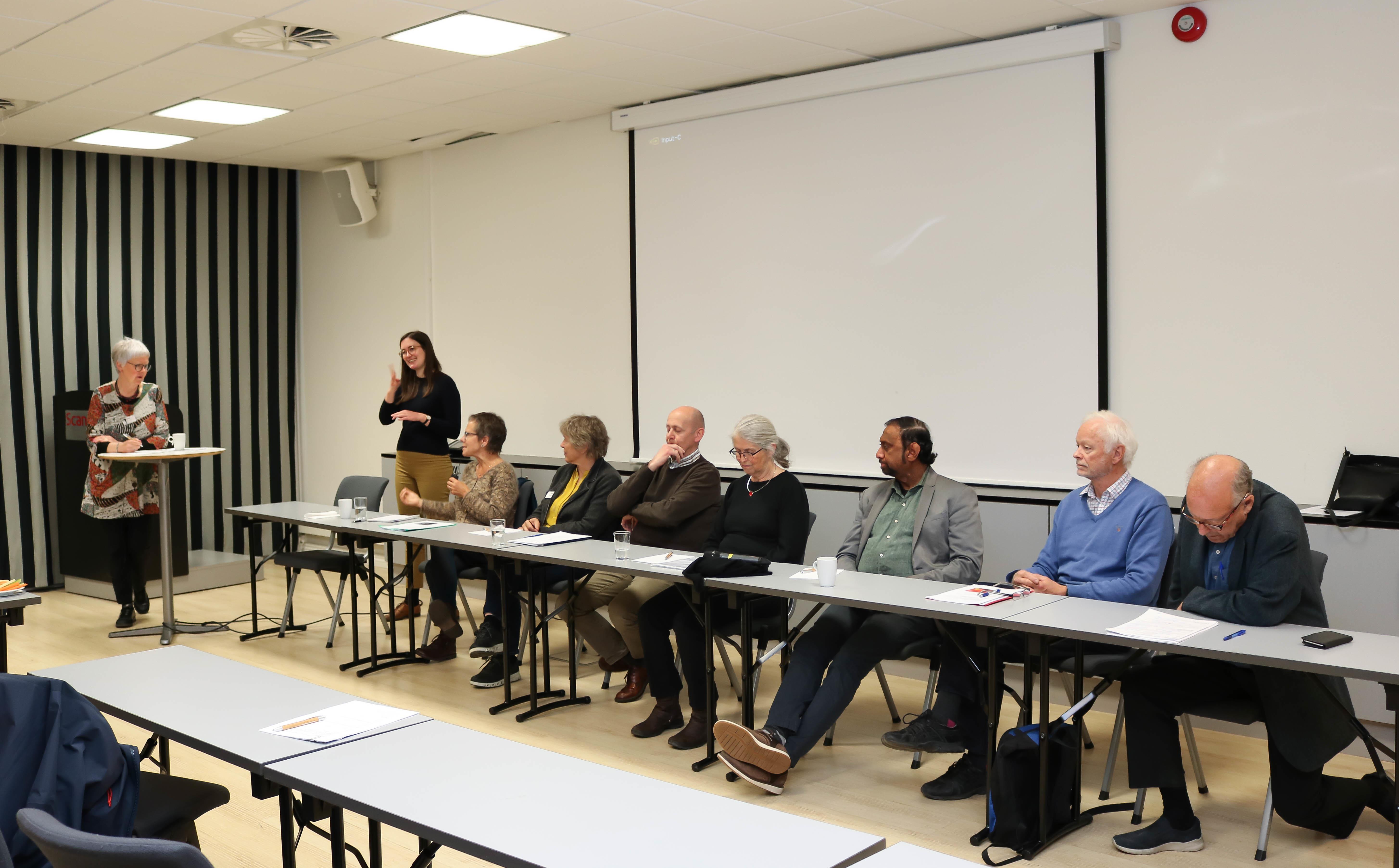 Fire menn og fire kvinner sitter på rekke og rad i en paneldialog. En kvinnelig tegnspråktolk står helt til venstre og tolker det som blir sagt.