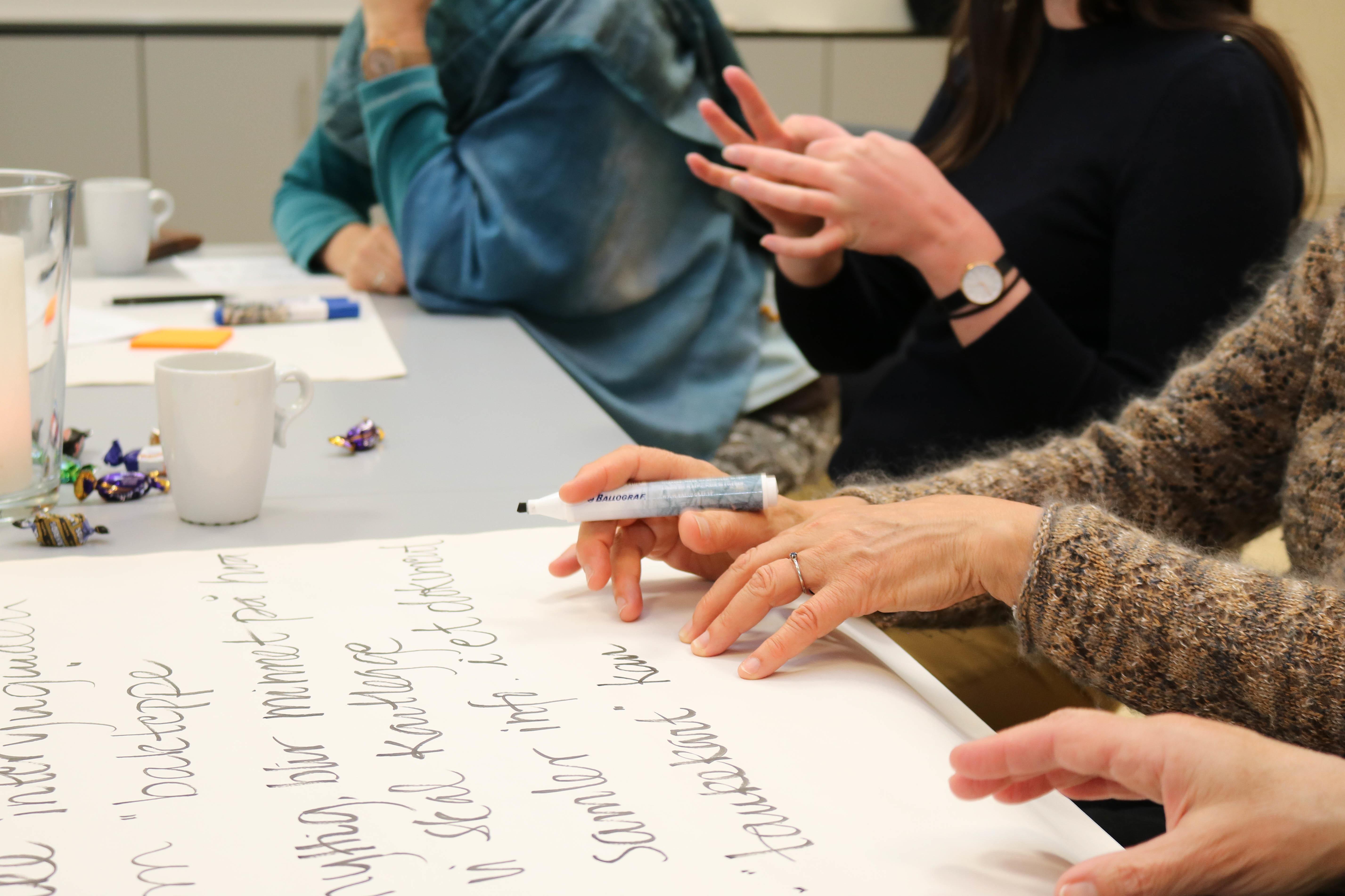 Arbeid under gruppearbeid, notater skrives på et stort ark mens det hele blir tegnspråktolket.
