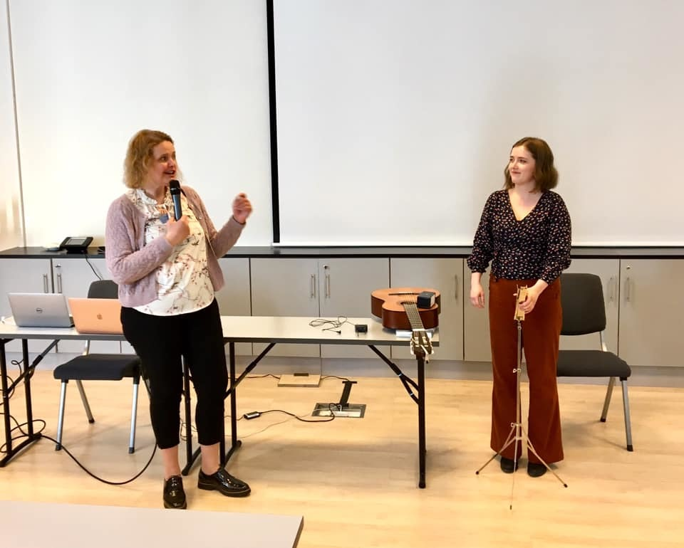 To kvinner prater med hverandre fremst i en konferansesal. En gitar ligger mellom dem på et bord.