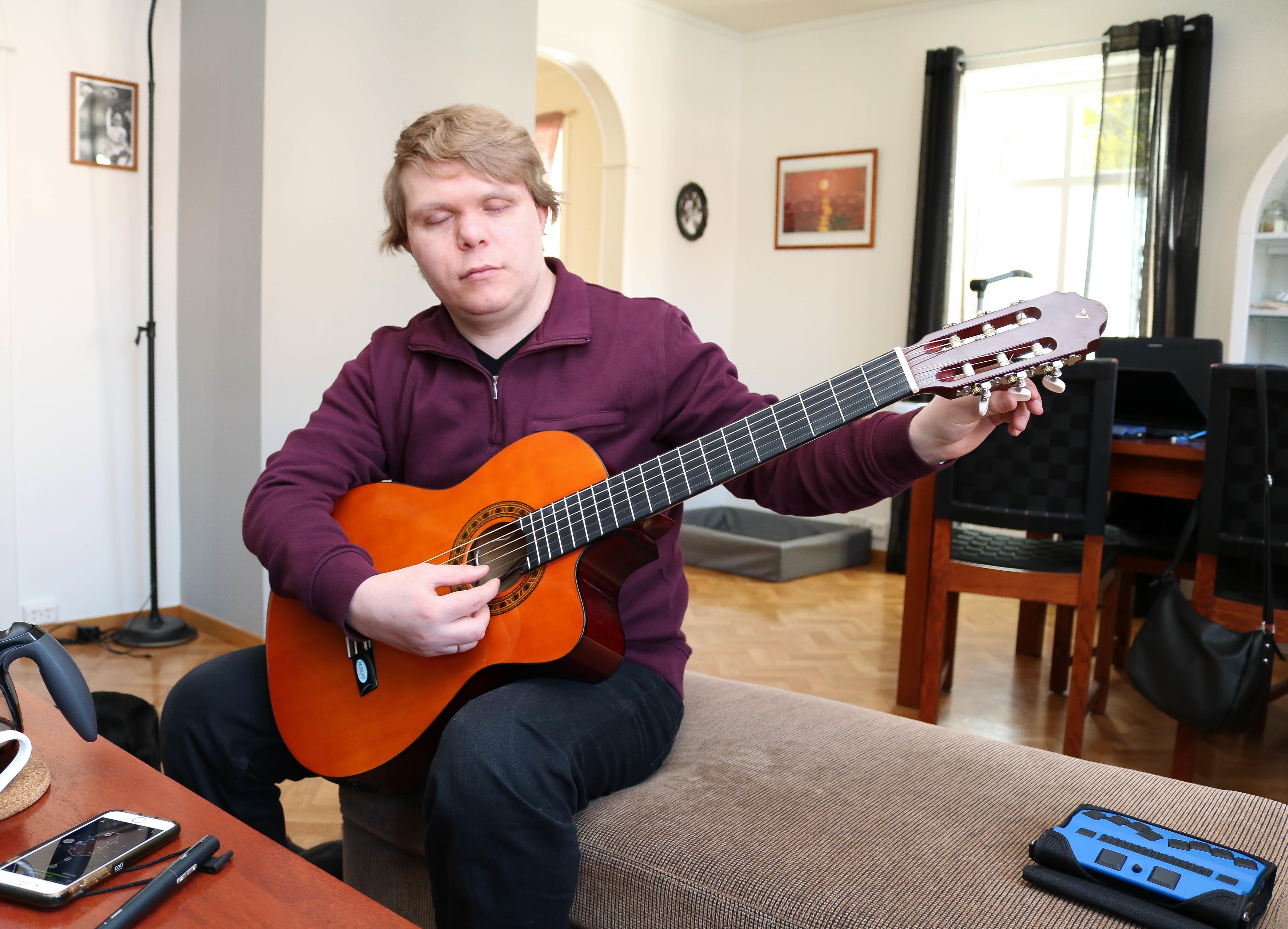 Døvblind mann med lilla genser sitter i sin stue og spiller på en gitar.