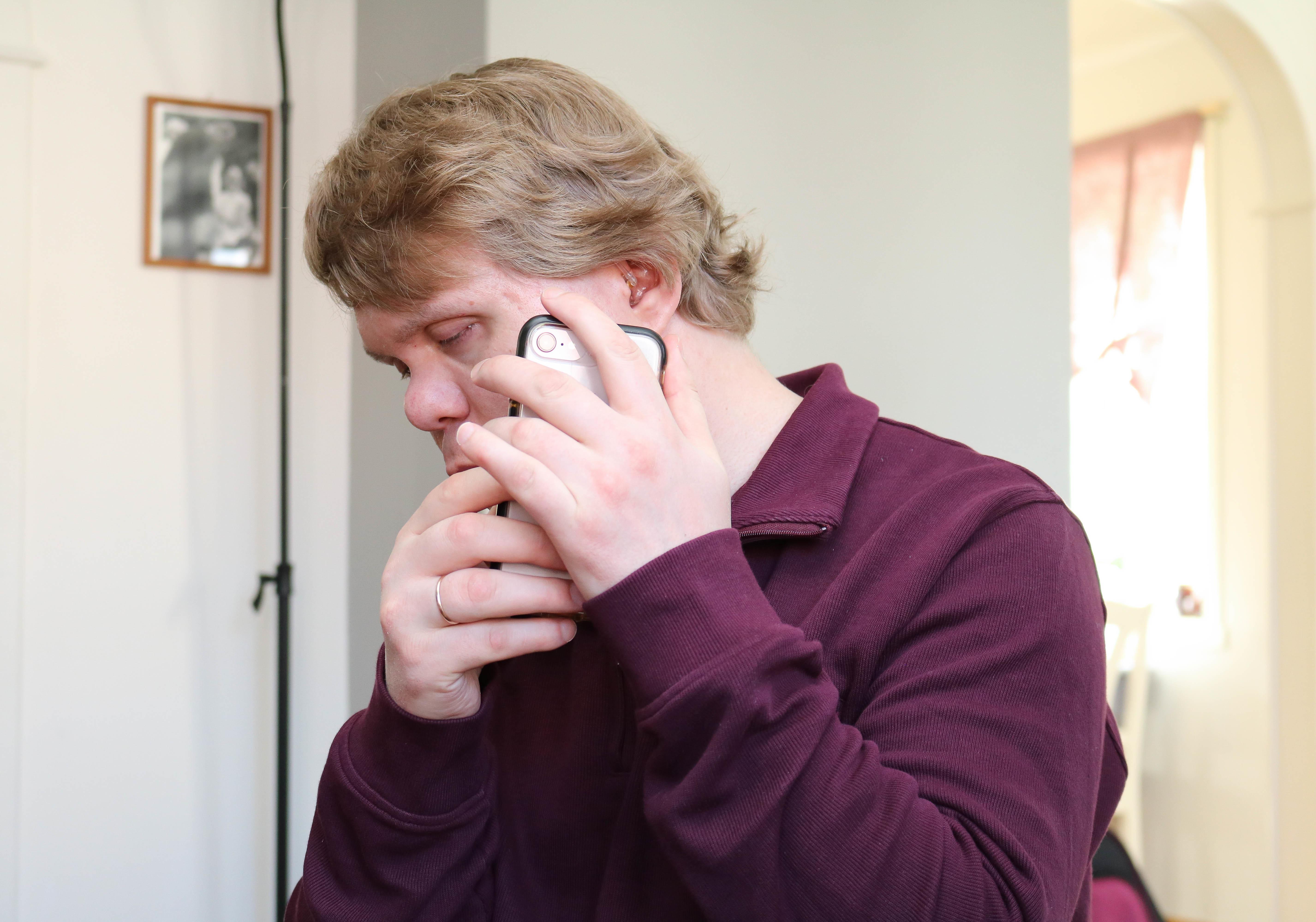 Døvblind mann med lilla genser hører på sin Iphone.