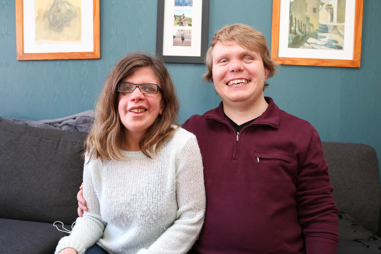 Døvblind mann i lilla genser, sitter tett sammen med sin kone i hvit genser i en sofa.
