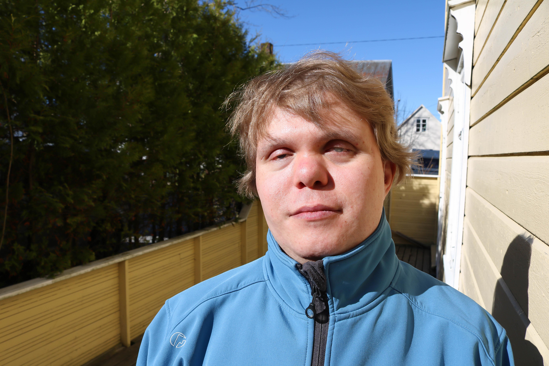 Portrettbilde av døvblind mann ved gul husvegg. Han har på seg en lyseblå fleecejakke.