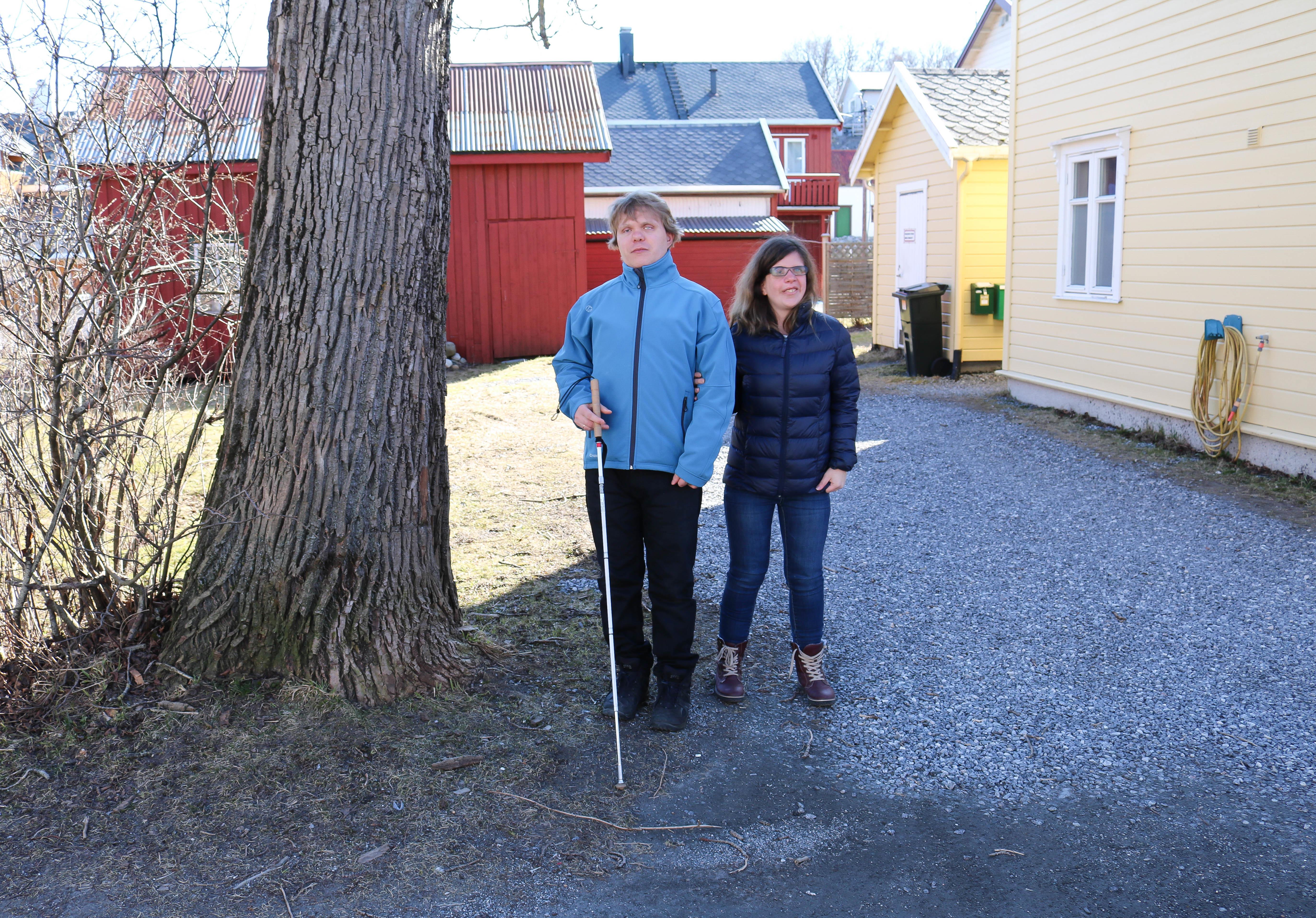 Døvblind mann med blindestokk og hans kone, står i innkjørselen til et gult hus.