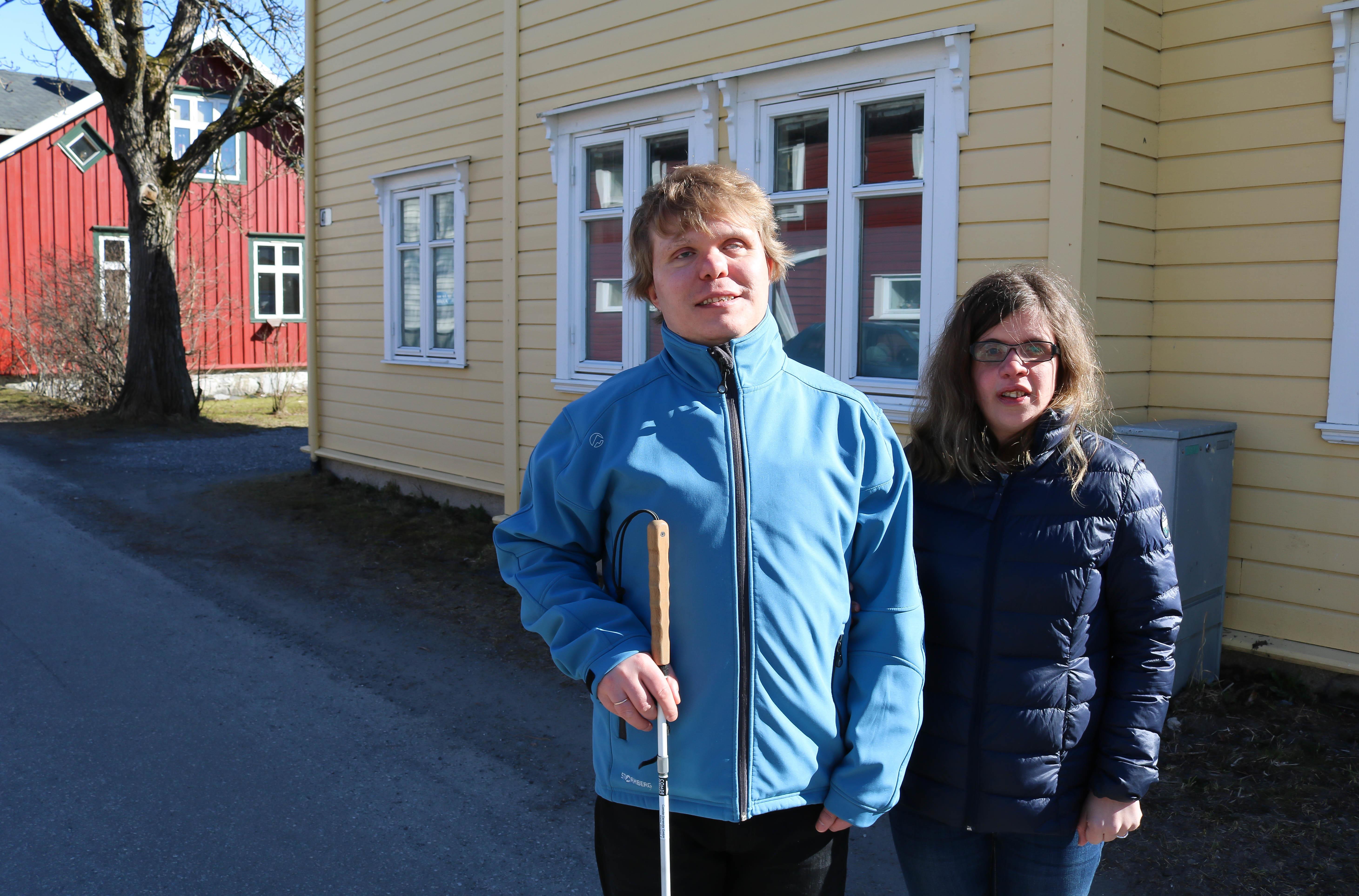 Døvblind mann med blindestokk og hans kone foran et gult hus.