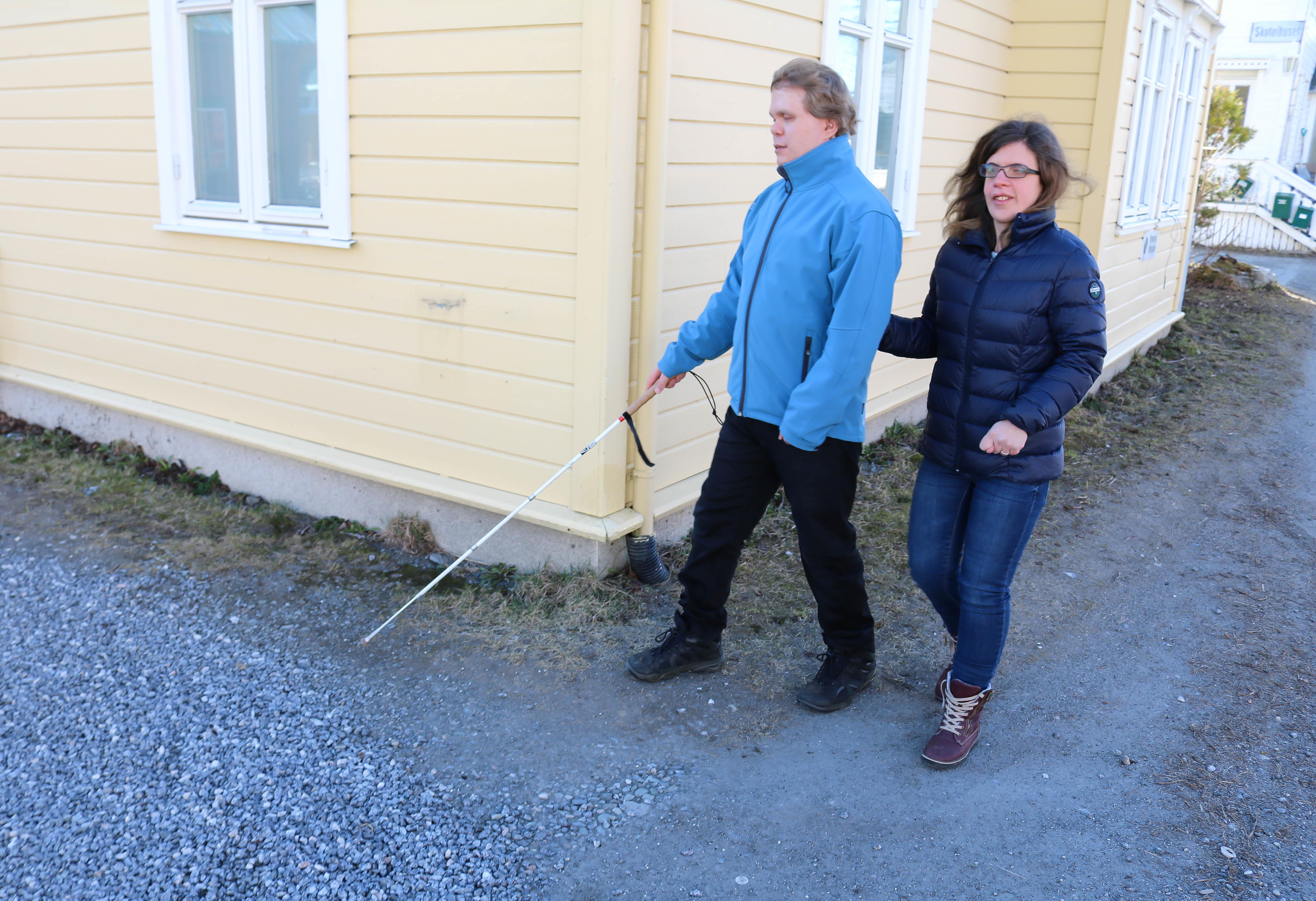 Døvblind mann med blindestokk går med sin kone forbi et hushjørne.