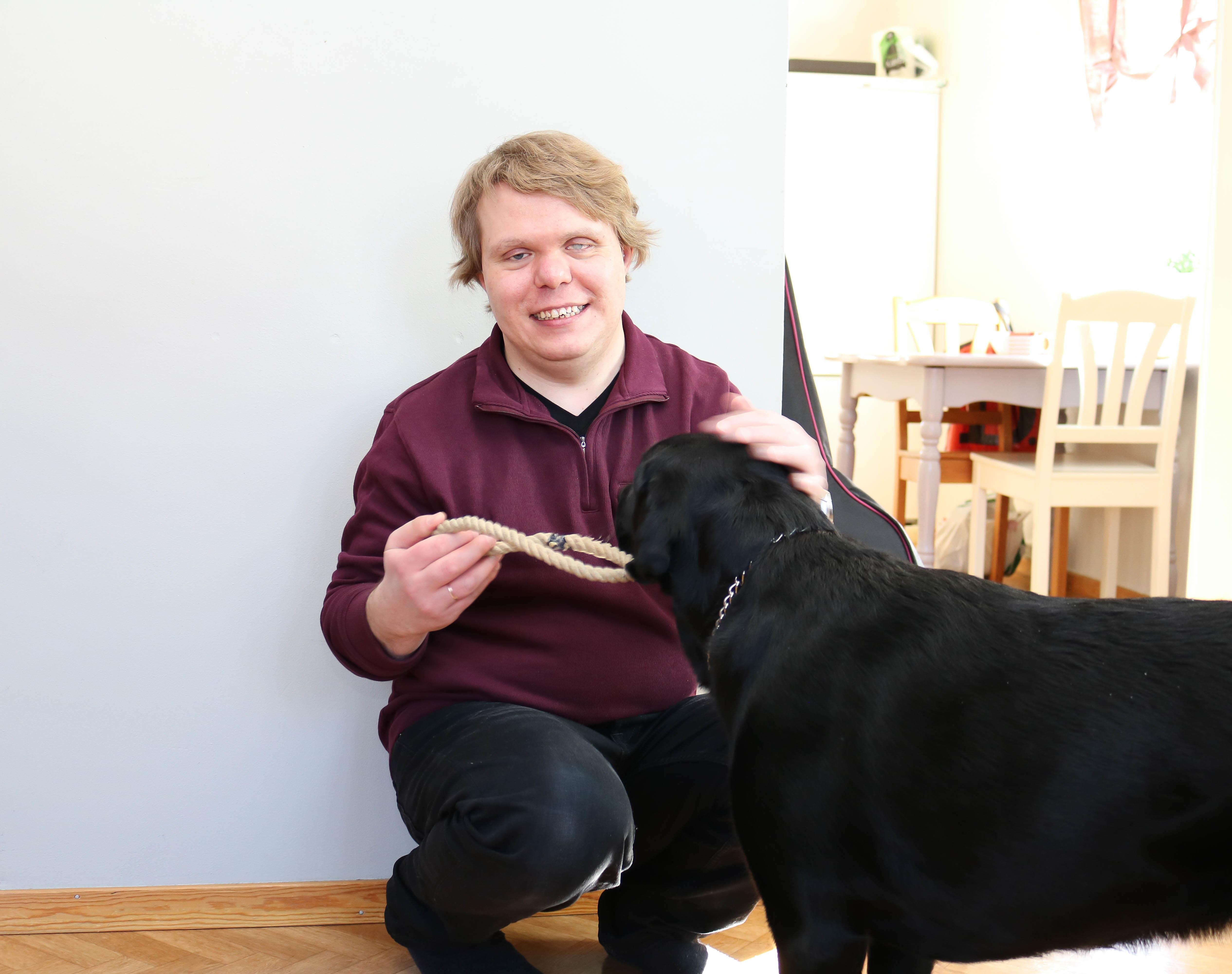 Døvblind mann med lilla genser sitter på huk, og leker med en svart førerhund.
