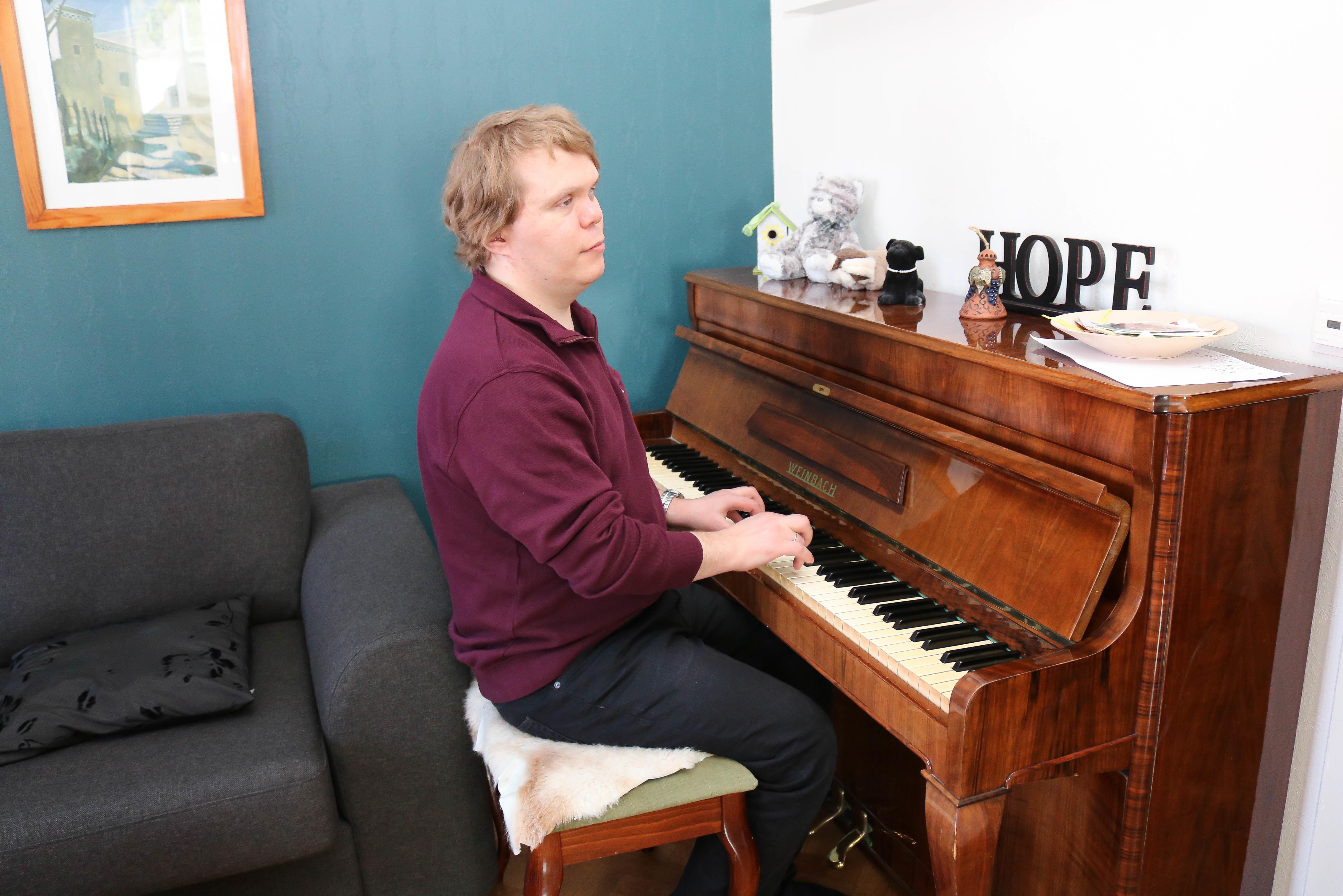 Døvblind mann med lilla genser spiller på et opprettstående piano.