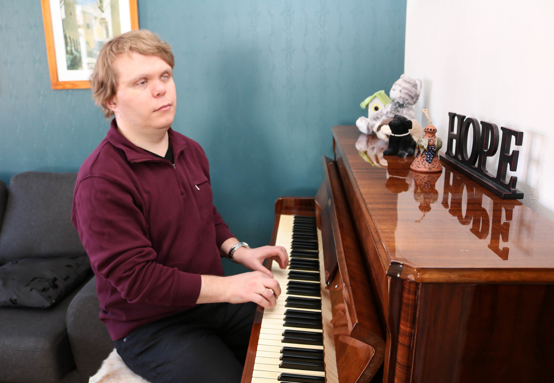 Døvblind mann med lilla genser spiller på et opprettstående piano. Øverst på pianoet står det med store bokstaver: Hope.