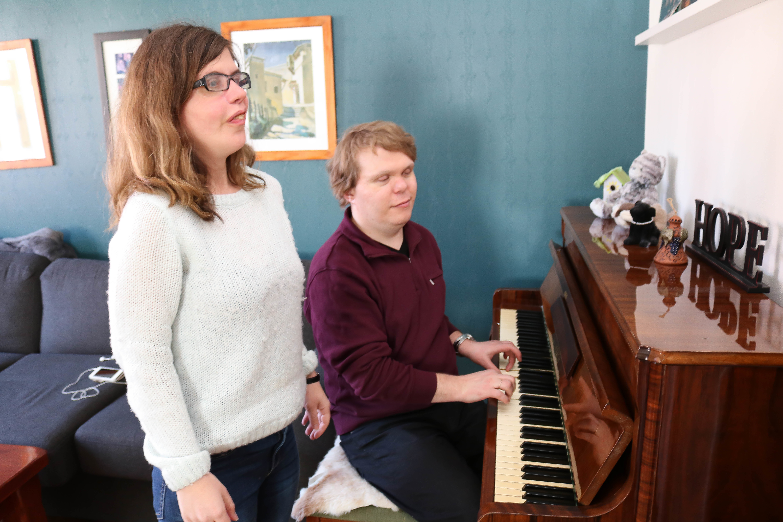 Døvblind mann med lilla genser spiller på piano, mens hans kone i hvit genser står ved hans side og synger.
