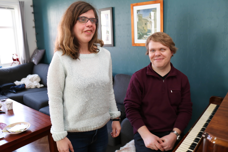 Døvblind mann med lilla genser sitter ved et piano i en stue, sammen med sin kone i hvit genser.