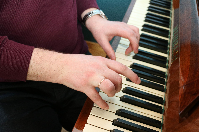 Nærbilde av hender som spiller på piano.