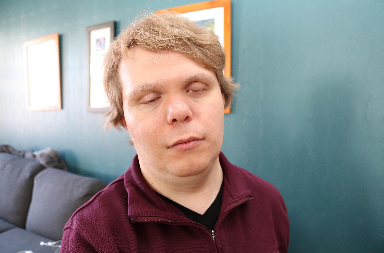 Portrettbilde av døvblind mann med lukkede øyne, mørkeblå bakgrunn.