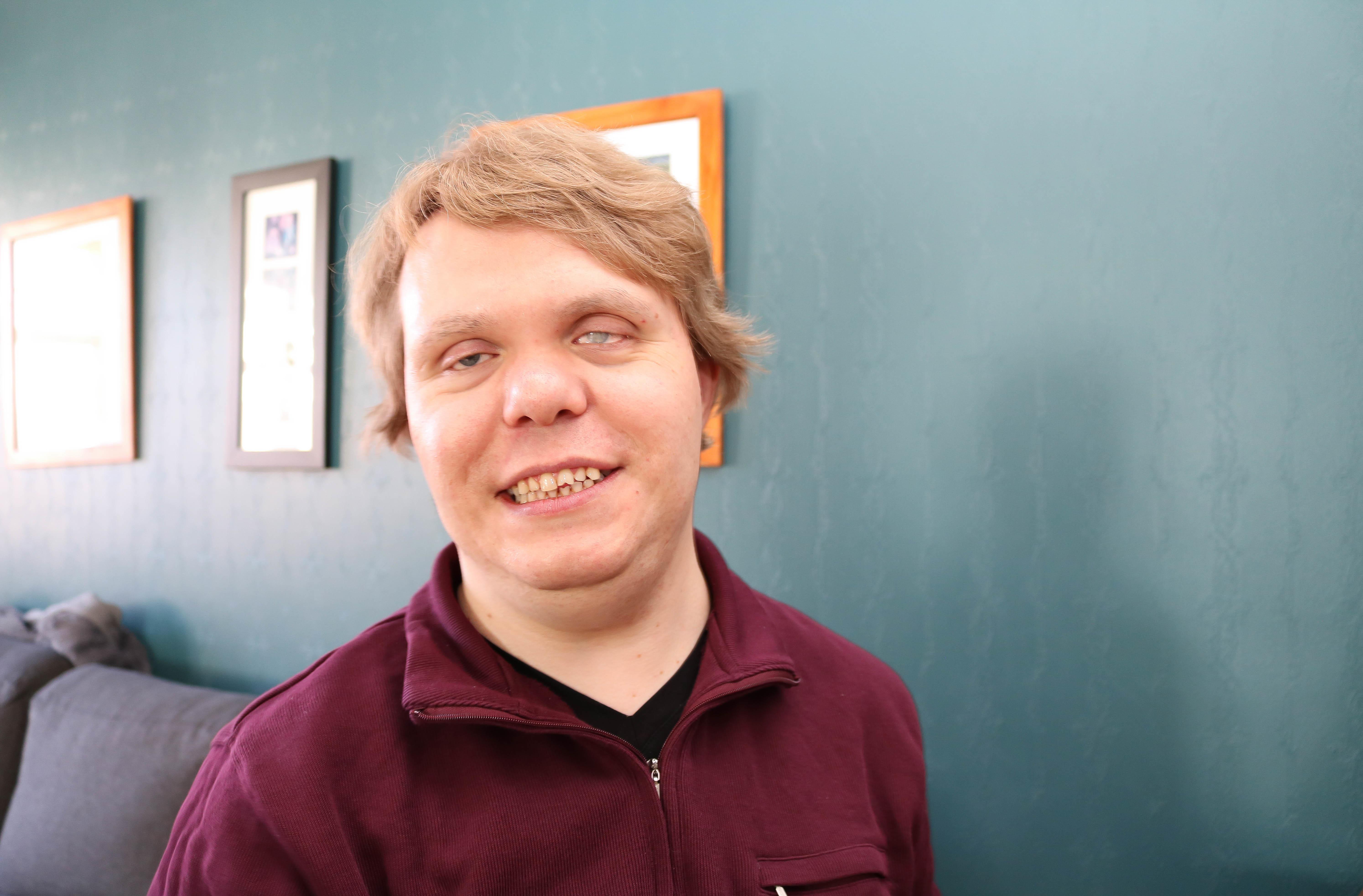 Portrettbilde av smilende døvblind mann, mørkeblå bakgrunn.