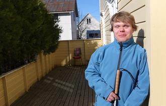 Portrettbilde av døvblind mann ved gul husvegg. Han har på seg en lyseblå fleecejakke og holder en blindestokk mot sin mage.