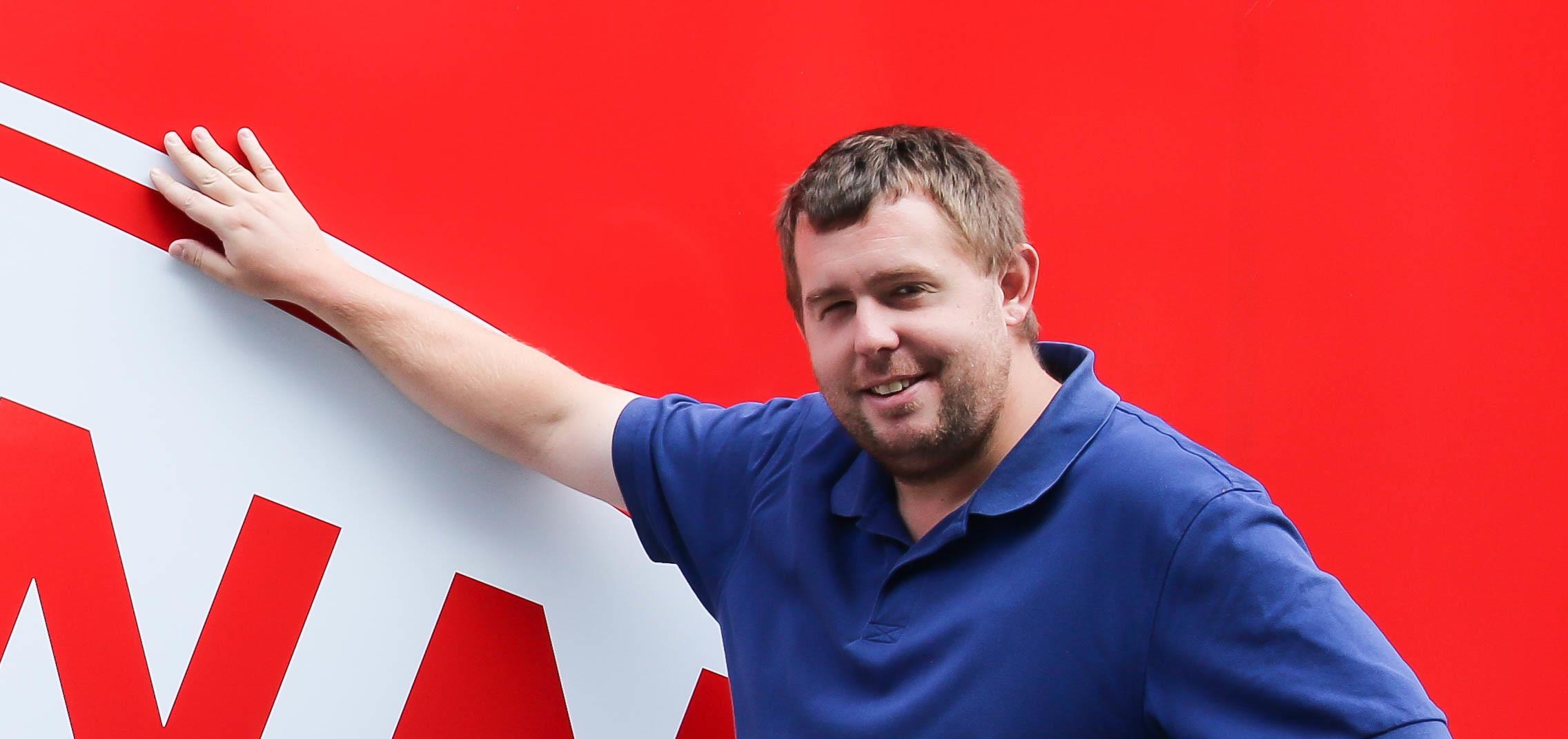 Mann poserer foran en vegg med logoen til sportsklubben Brann.