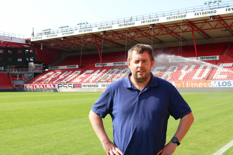 Mann i blå piquet poserer inne på Brann stadion i Bergen.