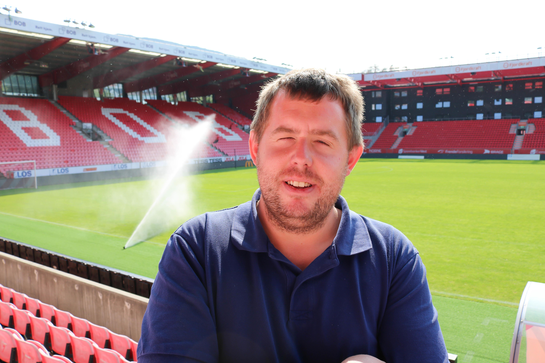 Mann står på tribune inne på Brann Stadion.
