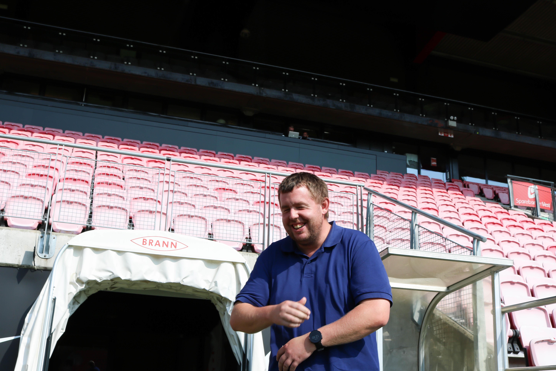 Mann ler godt foran spillerinngang og tribune inne på Brann stadion.