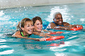 Multi-ethnic group of mature women having fun in swimming pool, kicking and splashing while racing, hanging on to kickboards.  Focus on the woman on the left.