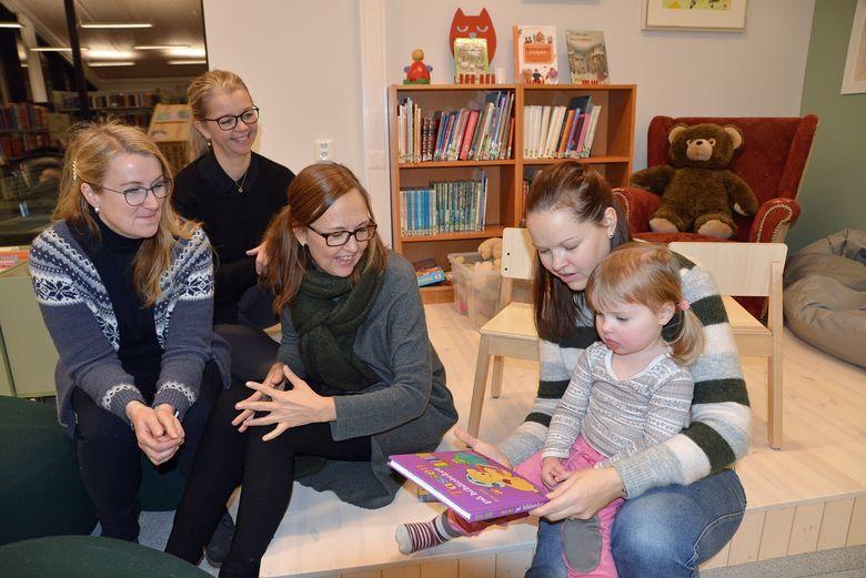 Bilde av mor og barn sammen med ansatte ved helsestasjons- og skolehelsetjenesten som leser bok