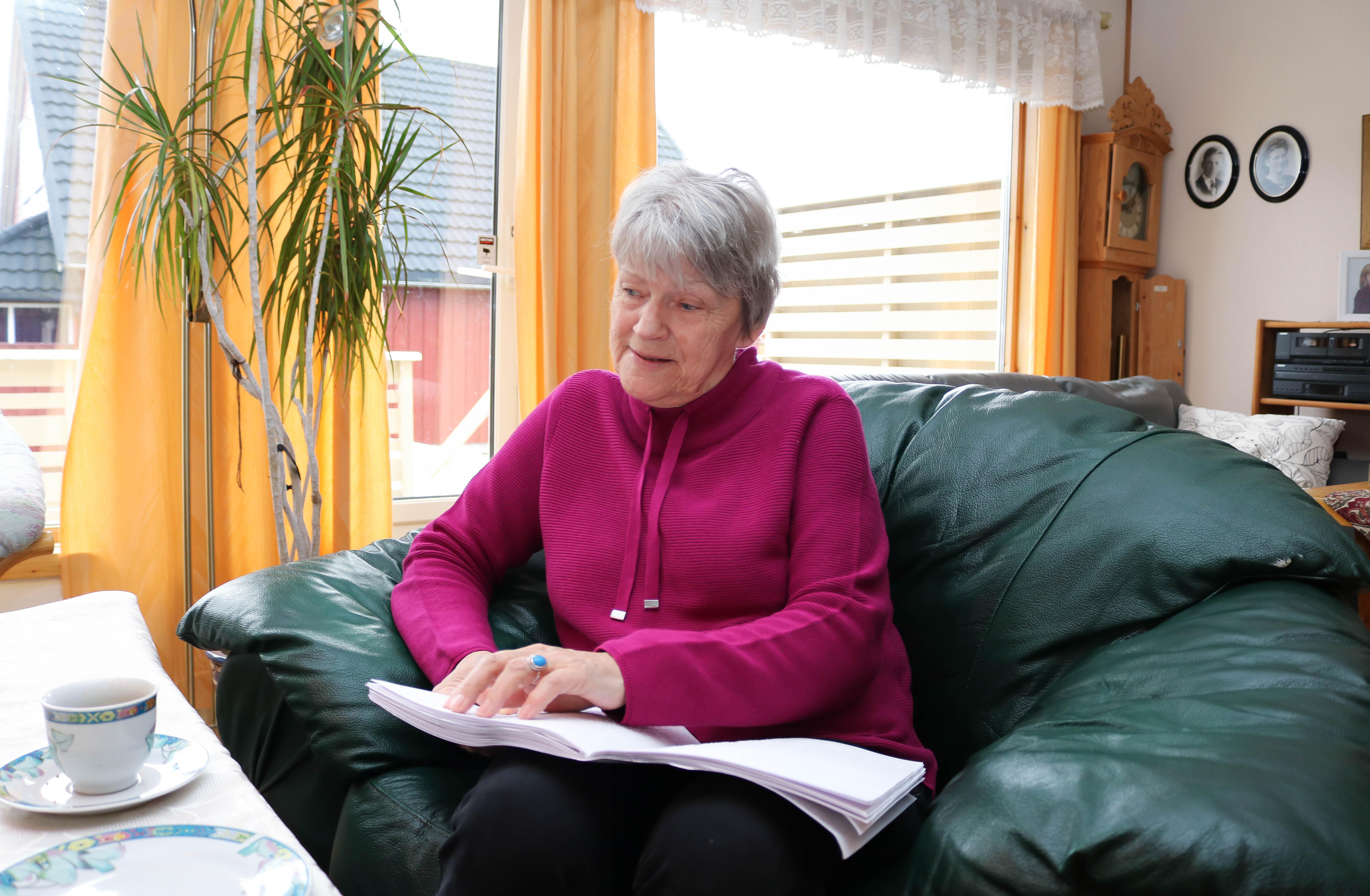 Kvinner sitter i lenestol og blar i en avis.