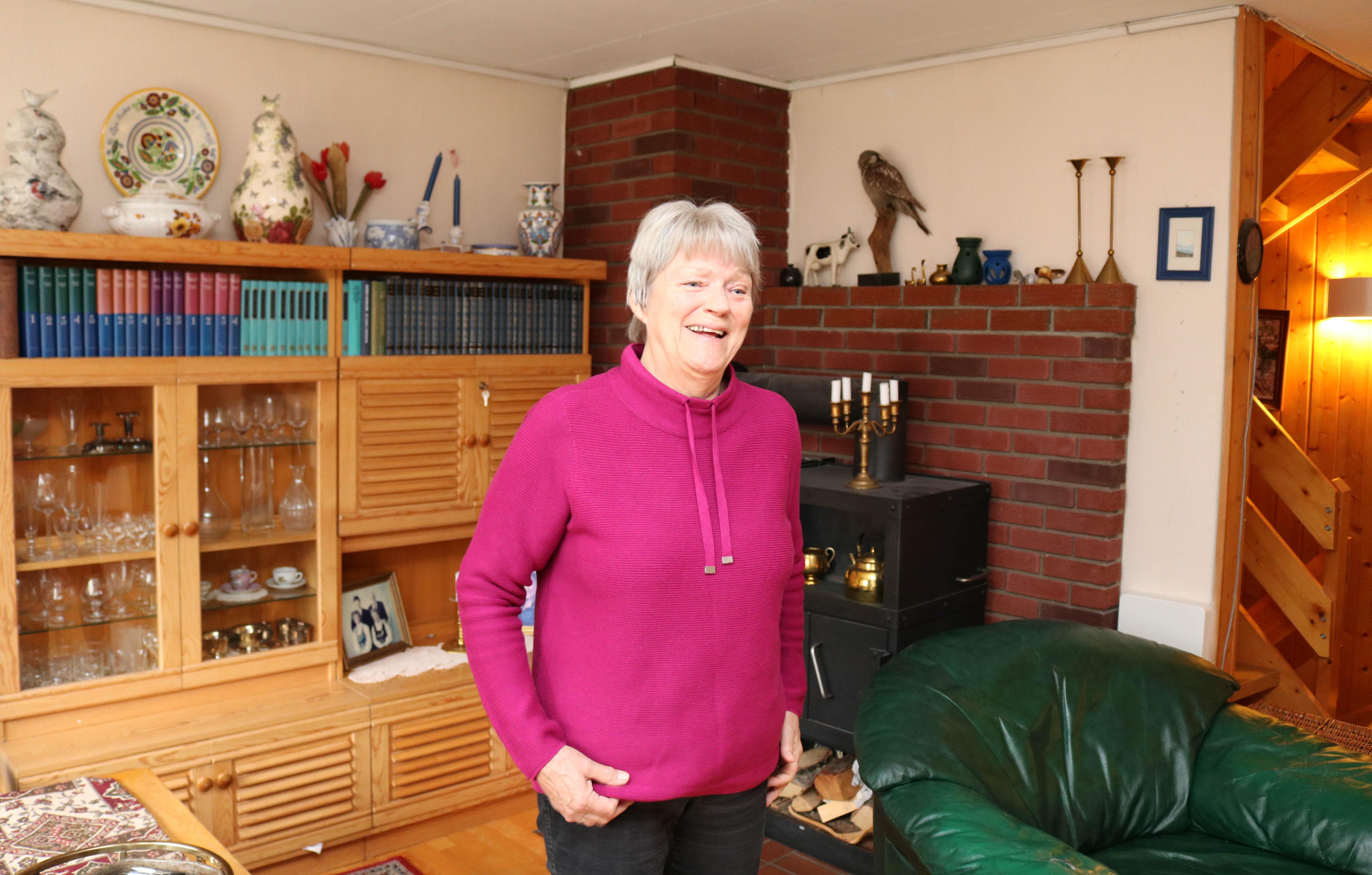Kvinne i rød-lilla genser står foran vegg-til-veggseksjonen i sin stue.