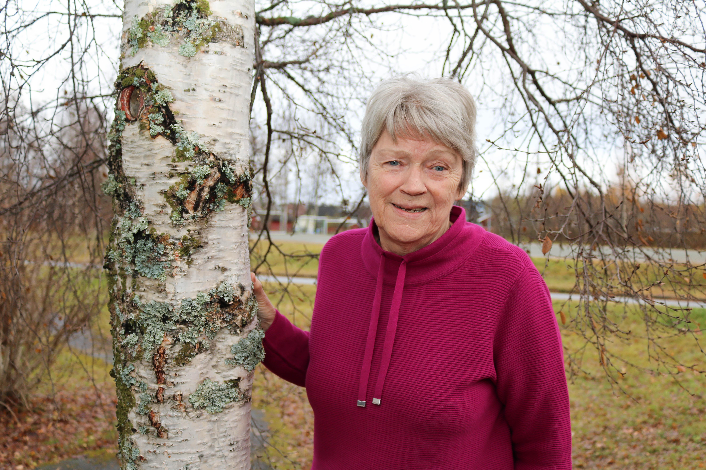 Døvblind kvinne står ute ved et bjørketre.