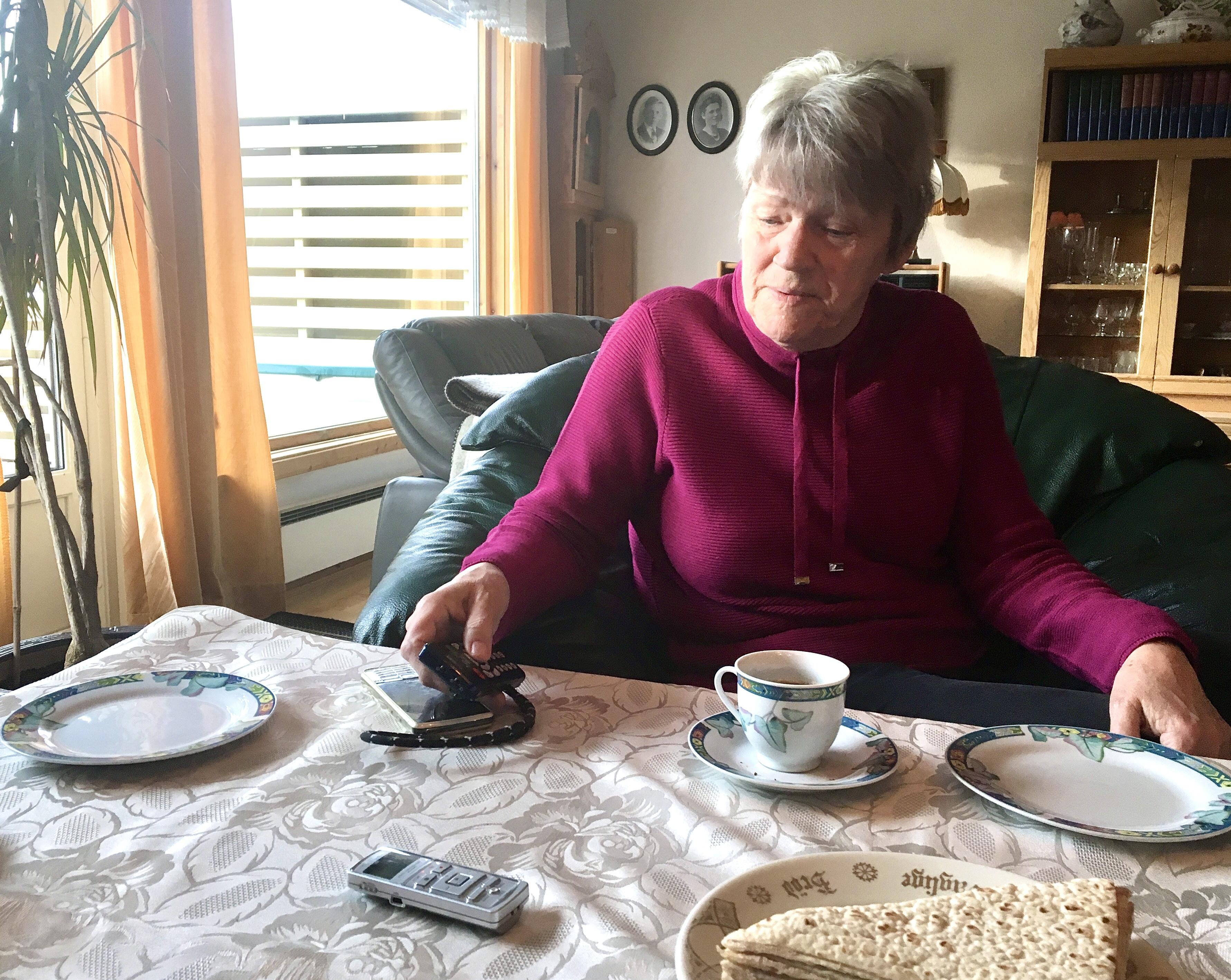 Kvinne ved sitt stuebord, hun viser fram diverse teknisk utstyr.