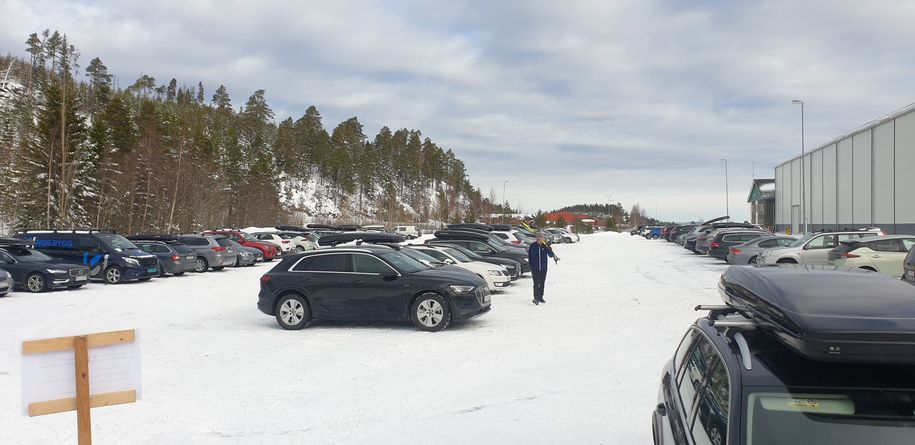 Bilde fra parkeringsplassen ved Abrahallen, med mange biler.