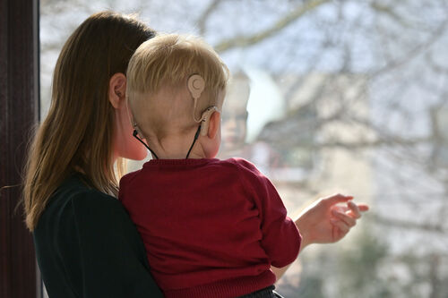 Gutt med CI som sitter på mors arm.