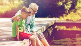 Bilde av en mann og gutt som sitter på bryggekant
