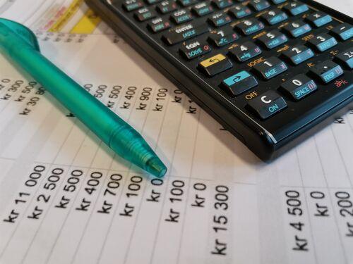 Et ark med budsjett. En penn og en kalkulator ligger oppå.
