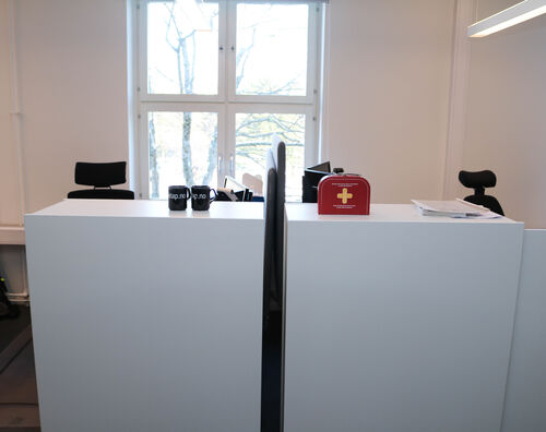 To arbeidsstasjoner mot hverandre, foran et avlangt vindu. Et rødt førstehjelpsskrin står øverst på den ene arbeidsstasjonen.
