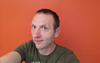 Mann tar selfi med oransje bakgrunnsvegg.