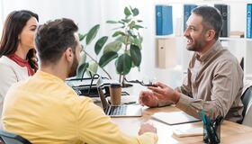 Tre personer som sitter og snakker over et bord med en formell og lett tone