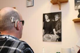 Døvblind mann med CI har blikket rettet mot en vegg, hvor han selv er avbildet på en plakat.