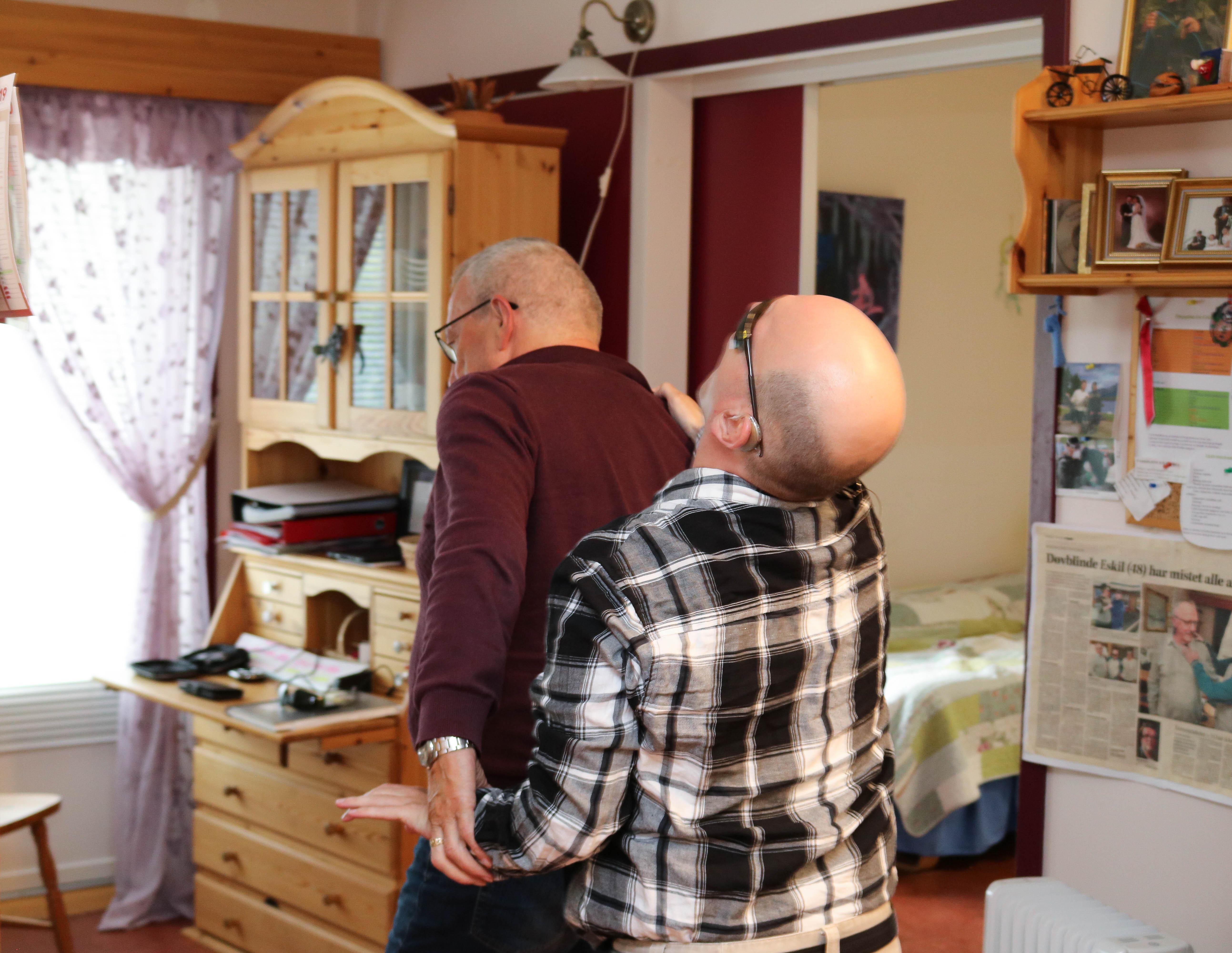 Døvblind mann går bak ryggen på sin far gjennom en stue.
