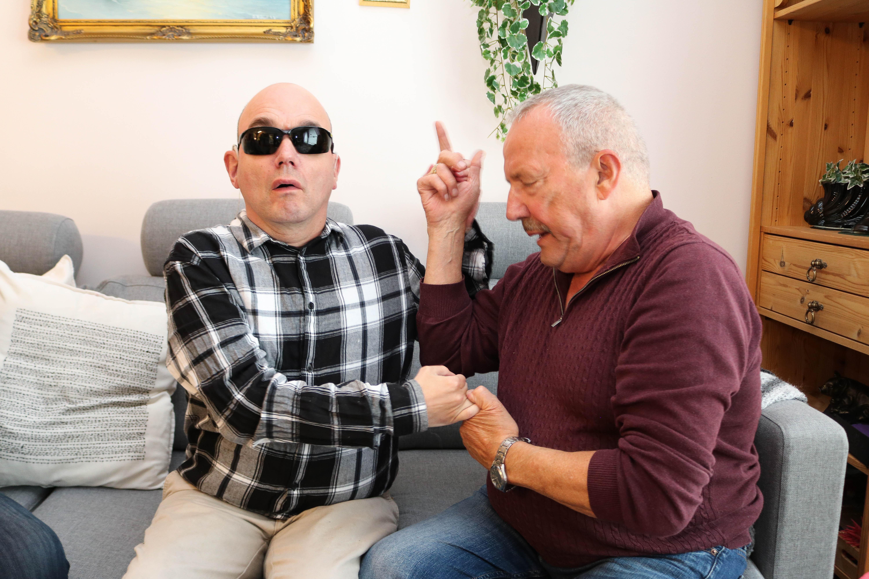 Mann kommuniserer med sin voksne døvblinde sønn gjennom taktile tegn.